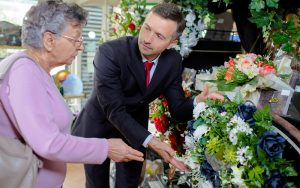 Man helping woman with flowers